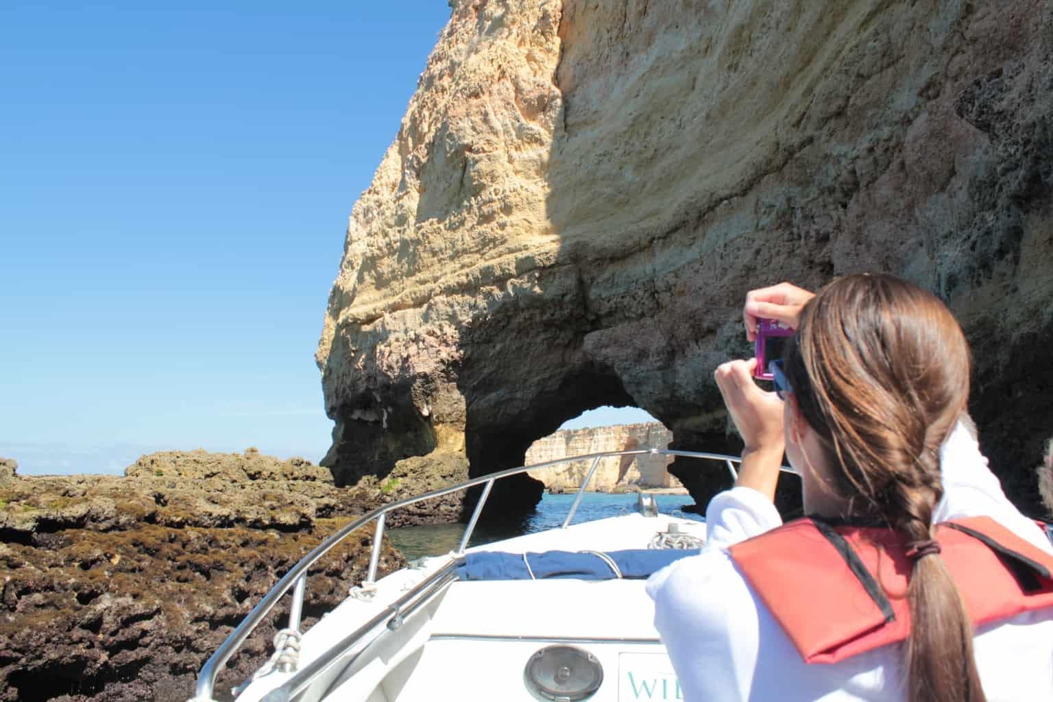 passenger on a boat taking a picture to the cliffs