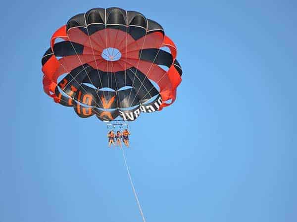 3 guests enjoying a triple parasailing flight