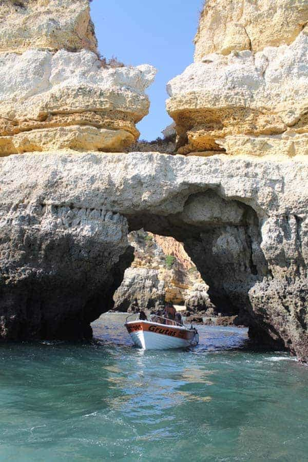 Boat passing an arch through the rocks