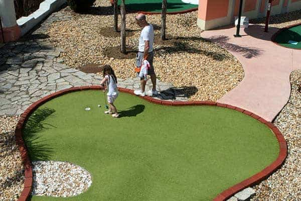 Little girl learning to play in Vilamoura Mini Golf