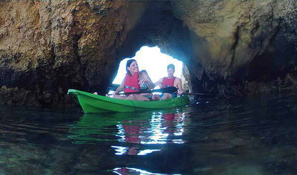 two people on a green kayak leaving a cave