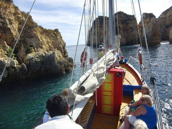 Traditional sailing boat passing big cliffs near Alvor