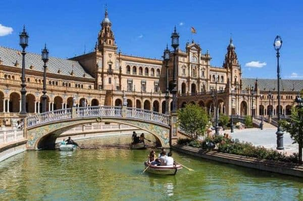 seville cathedral with bosts on the river and small bridge