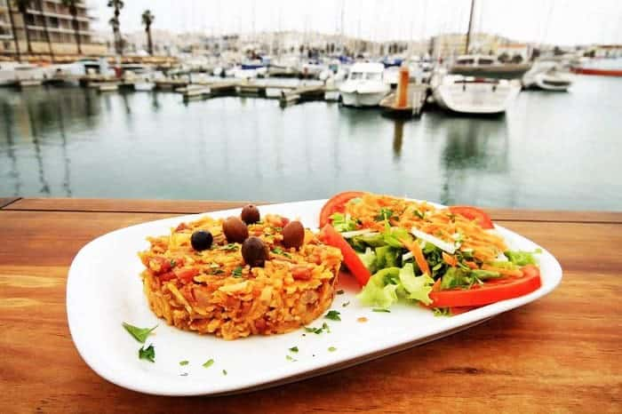 Rota Do Petisco rice with olives on top dish and salad overlooking the Marina